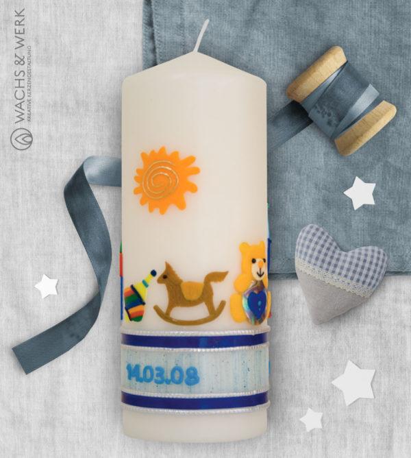 Kerze zur Geburt mit Wiege und Spielzeug